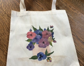 Hand painted pansies in a vase on a cream canvas tote.
