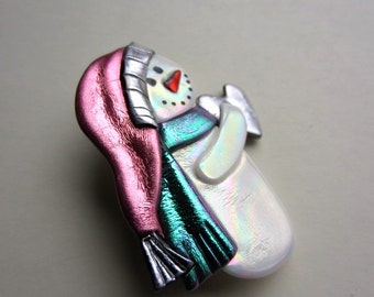 Snowman with pink stocking cap and scarf holding a heart pin brooch