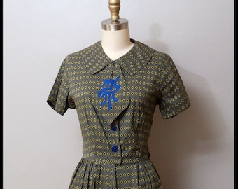 vintage 1950s shirtwaist dress with large ascot with Asian symbo