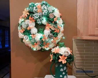 LIGHTED St. Patricks Day Wreath, and matching centerpiece mug,white and green Carnations, Orange tiger lilies,coins, glitter Shamrock center