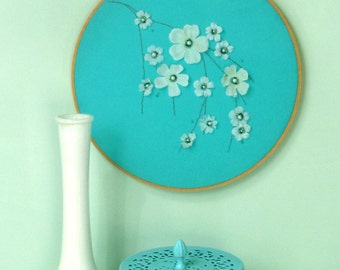 Hoop art of white blossoms branch with beaded embroidered flower centers on aqua blue fabric