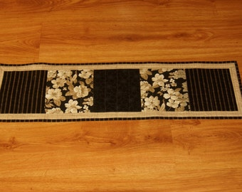 Quilted Table Runner and Four Drink Coasters of black fabric with shade of Off  White, Cream  and Tan made by Barb Lynn.