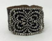 Brown leather cuff with Fleur de Leis design embelished with  vintage steel cut shoe buckle.