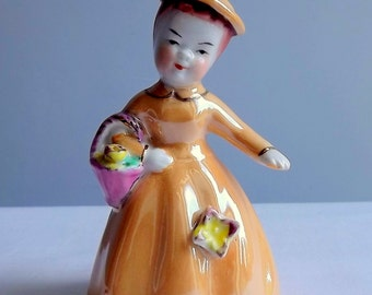 Ceramic lady bell in pale orange dress and hat