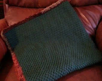 Green honeycomb textured baby blanket with multi-colored shell border