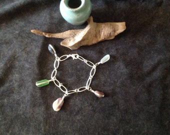 Sterling silver charm bracelet with seashell ,beach stone ,and Sea glass charms.  7 1/2 inches.