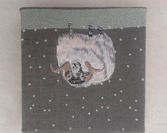 Embroidered picture of a ram in the snow