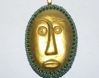 Gold Polymer Clay Tribal Face Pendant, Green Bead Bezel, Gold Tone Bail, Gold Satin Cord Necklace