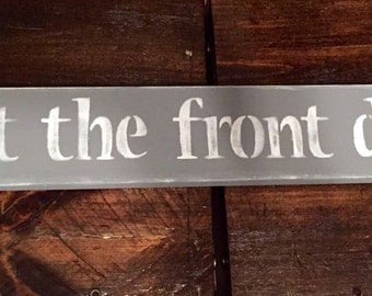 4x24 hand painted wood sign. Shut the front door!! Funny, cute sign Done in black with white lettering. Hung with 2 sawtooth hangers on ends