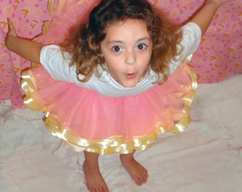 Pink tulle tutu skirt trimmed in sunny yellow satin ribbon.