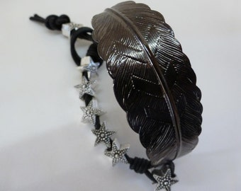 Patinated etched copper feather binds black Greek leather to studded silver aluminum stars to create Floating Stars Bangle