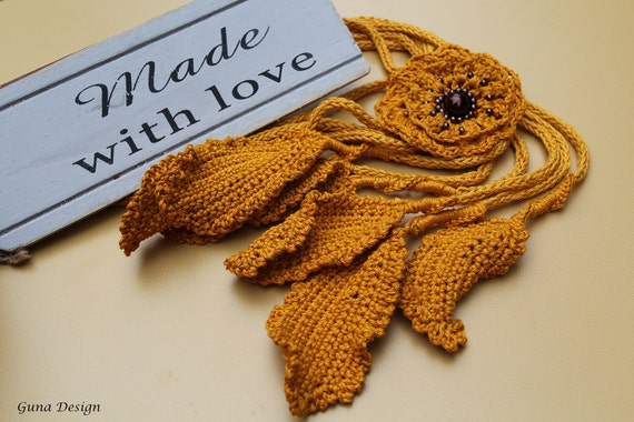 Crochet yellow e cord style lariat necklace with with flower decorated with beads and leaves