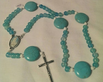 Blue stone and glass rosary on white babmboo