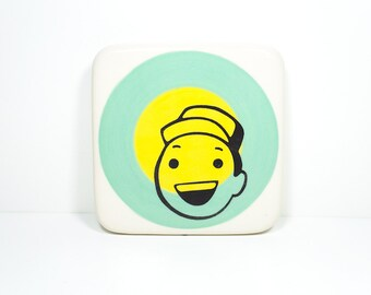 "tile with a dude we think is saying ""Hey!"" on colour block of blue green and yellow, made to order."