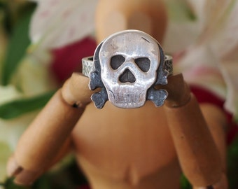 A skull and crossbones ring made from solid silver.. perfect for Halloween.