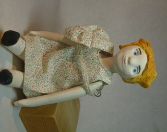 Doll articulated earthenware as formerly. Red hair, Hat Sun around the neck.