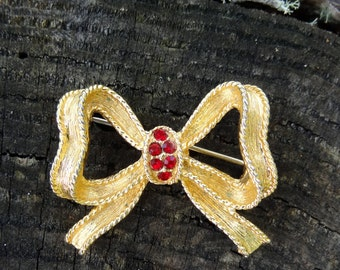Gold tone bow brooch , with red  rhinestones