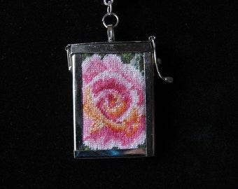Rose needlepoint tapestry in a silver hinged frame, pendant necklace with pink leather cord