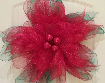 Poinsettia Christmas wreath made of red and green mesh and ornamental ties.