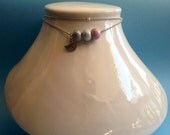 Ornate silver necklace 3 ceramic beads and a charm.