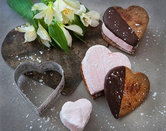 Heart shaped s'mores made from a hand crafted pink marshmallow sandwiched between homemade graham crackers dipped in rich dark chocolate