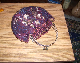 Red satin evening bag with numerous beading and two handlers