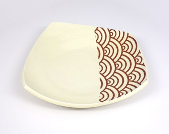 Squared porcelain platter with creamy yellow glaze and wave pattern