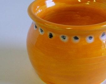 Orange wheel thrown pot with a White and Black Dot patter around the top edge.