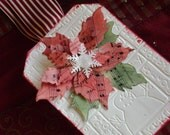 single poinsettia Christmas tag vintage sheet music inked red and green on an embossed white base