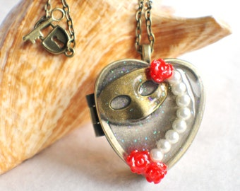 Music box locket,  heart shaped  locket with music box inside, in bronze with masquerade ball mask, pearls and roses.