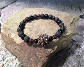 "Karma Exchange ""Touch of the Void"" Garnet, Obsidian, lava rock, and metal bracelet"