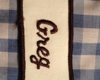 "Greg. A white work shirt name patch that says ""Greg"" in brown script with brown border"