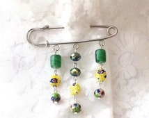Safety pin brooch with millefiori beads, green glass beads and green crystals