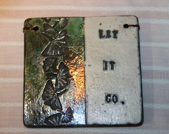 "Clay Quote Tile "" Let It Go"" with sigilated Ginkgo leaves, Raku varied colors contrast with white background. Black smoke lettering."