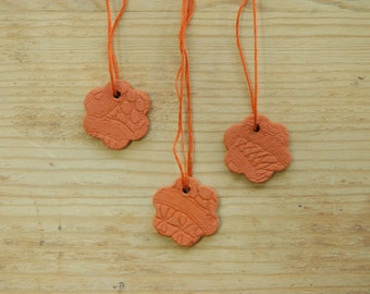 Set of three small sized red clay ceramic spring flowers ornaments with lace pattern.