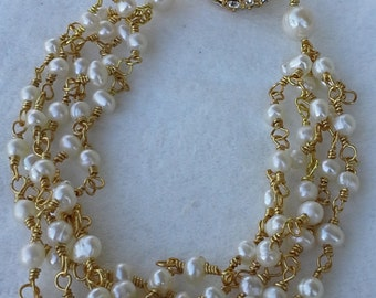 Handmade five  strands bracelet with  gold tone and fresh water pearls.