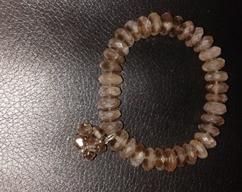 Natural frosted smoky quartz rondelle stretch bracelet with smoky quartz and sterling silver charm.