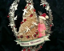 """This adorable ornament features a little girl in a Santa hat, hugging her tree. Tart tin base """"Merry Kissmas !"""" banner. MX07"""
