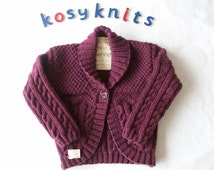 Hand knitted bolero style cardigan with shawl collar and cables in rich plum colour to fit approx 2-3 years knitted in pure merino wool.