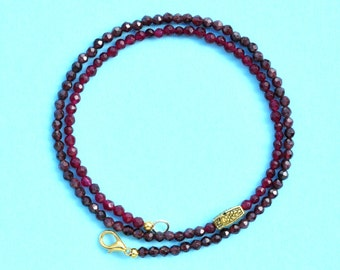 Sophisticated necklace of small, finely faceted red flashing translucent garnet beads, offset decorative brass bead and gold lobster clasp.