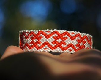 Red and white macrame bracelet with a Slavic ornament