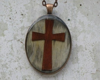 Weathered Maple wood background with Cherry cross overlay, resin encased in antique bronze finish pendant bezel with chain
