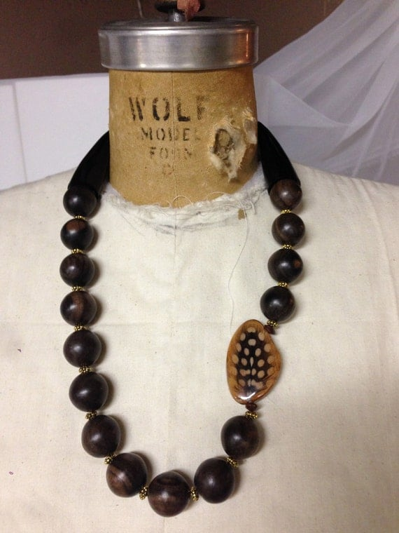 25 inch necklace with 20mm round black ebony wood beads interspersed w/ gold findings. Adorned w/ a Feather Inlay Laminated on Bayong Wood.
