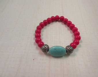 Great red beaded bracelet with turquoise howlite stone centerpiece.