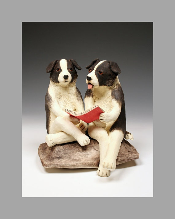 2 border collies sitting on a pillow, reading together, photograph of Pillow Talk, a whimsical sculpture by Florence Chik-Lau