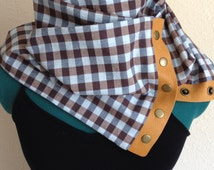 Fashionable, patterned infinity scarf with tan leather trim and antiqued brass snaps.