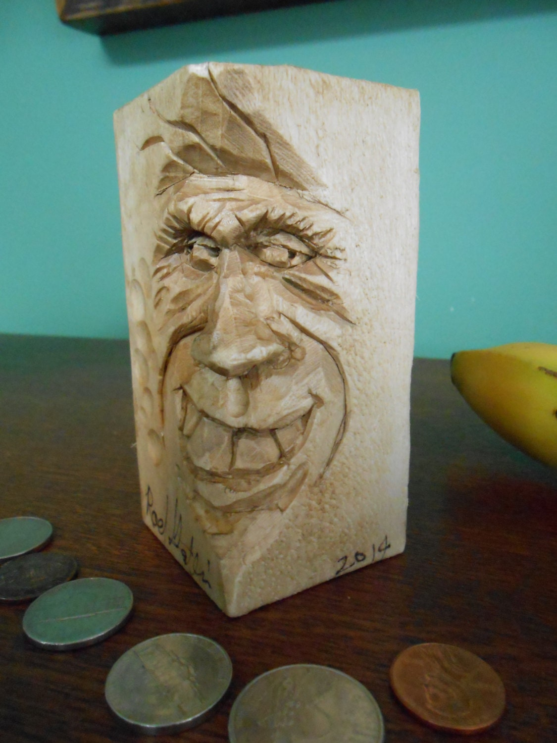 Hand carved wooden caricature face with shifty eyes big teeth