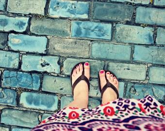 Feet on Cobblestones: fine art photograph print of self-portrait with colorful dress, flip flops, blue gray brick road in Old San Juan