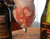 """Valentine's Day 12 oz wine glass hand painted with """"love"""" with a heart shaped O, pink base with red and white mini hearts"""