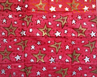 Sheet of red tissue paper handprinted with sparkly stars